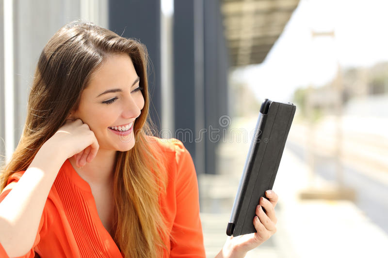 Woman reading a Tablet or ebook in a train station. Happy woman reading a Tablet or ebook in a train station while is waiting for public transport royalty free stock images