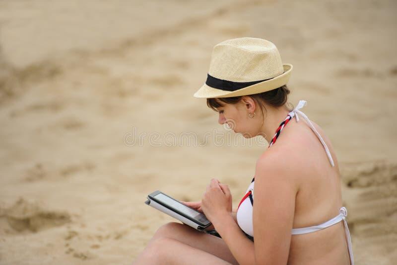 Woman reading tablet reader on the beach. Woman reading tablet reader on the sea beach, vacation, summer, bikini, technology, electronic, digital, ebook, e-book royalty free stock image