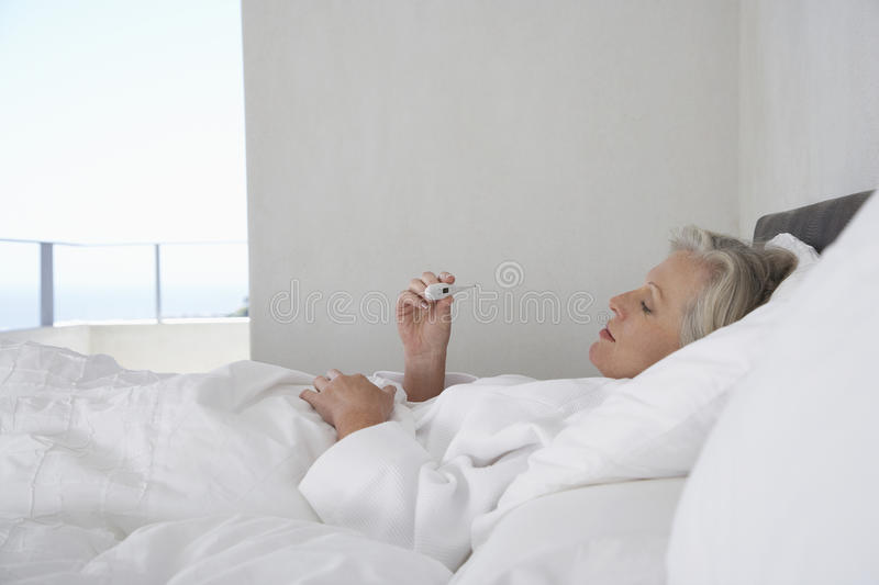 Woman Reading Temperature From Thermometer stock photography