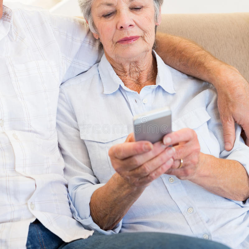 Woman reading text message on smartphone. Senior women reading text message on smartphone while sitting with men at home stock image