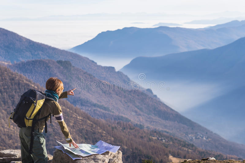 Woman reading trekking map and poiting finger to the Alps royalty free stock photo
