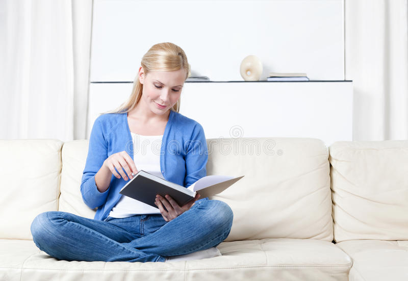 Woman reads the book lying on the sofa stock photo