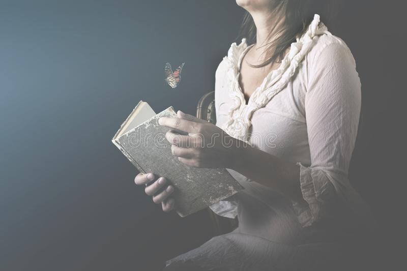 Woman reads a book where butterflies go out as a flow of dreams and thoughts stock images