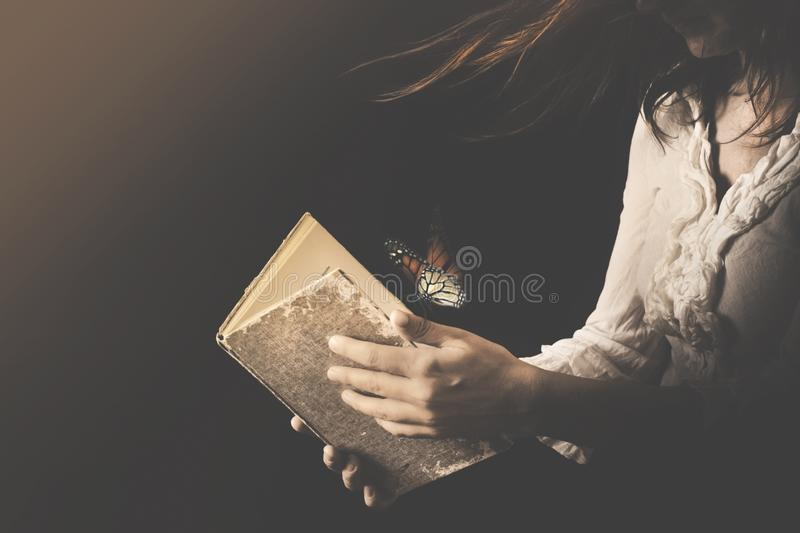 Woman reads a book where butterflies go out stock image