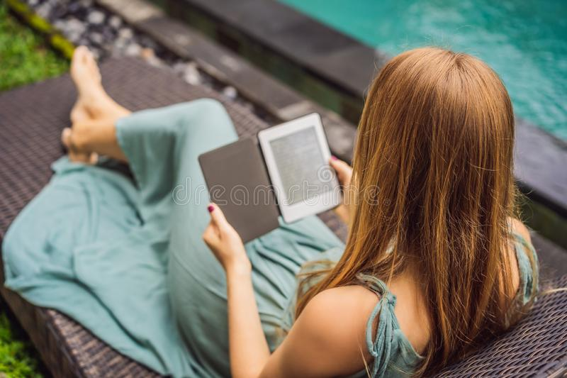 Woman reads e-book on deck chair in the garden.  royalty free stock photo