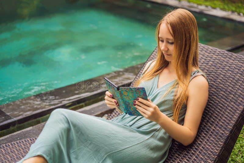 Woman reads e-book on deck chair in the garden.  stock photos
