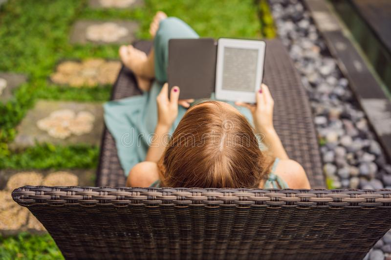 Woman reads e-book on deck chair in the garden.  stock photo