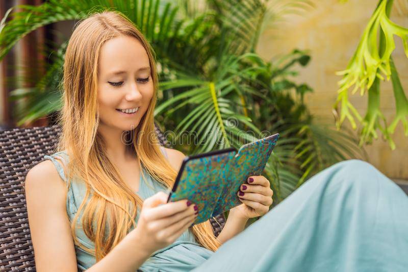 Woman reads e-book on deck chair in the garden.  royalty free stock photos