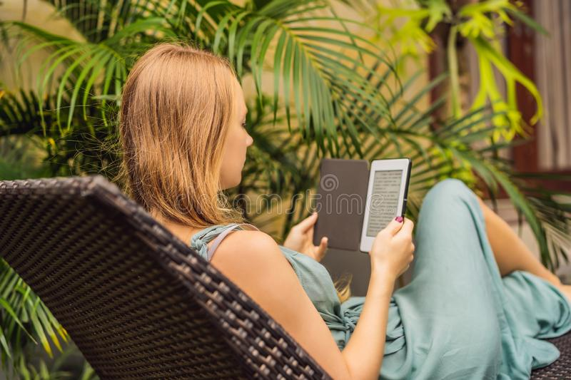 Woman reads e-book on deck chair in the garden.  royalty free stock image