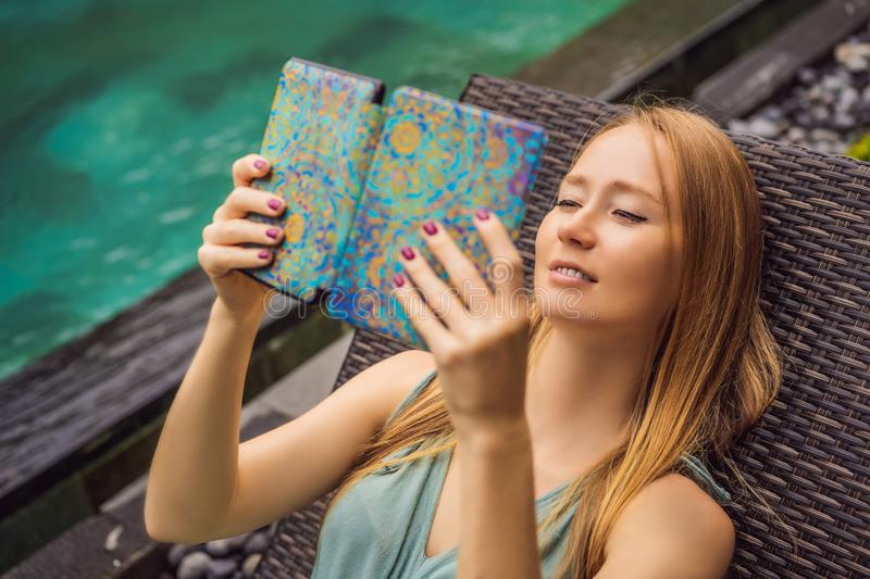 Woman reads e-book on deck chair in the garden.  royalty free stock images