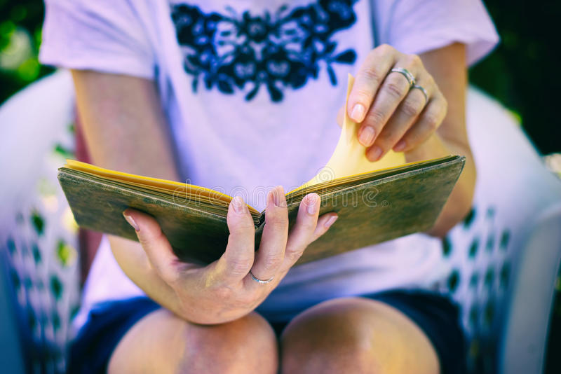Woman reads an old book in leather binding stock photos