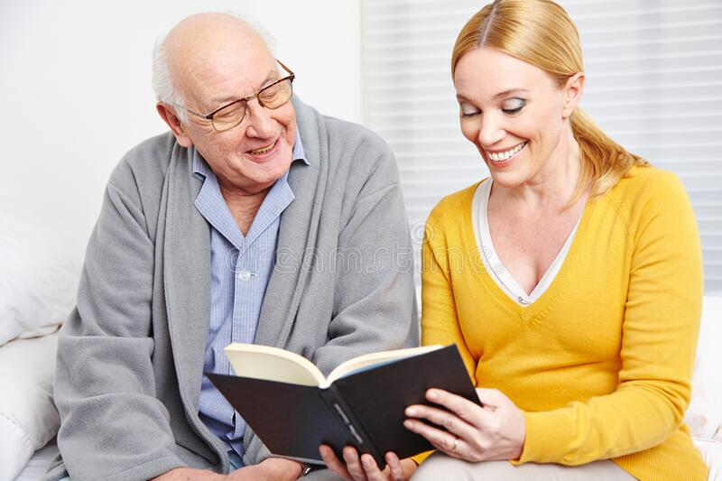 Woman reads senior stories from book stock image