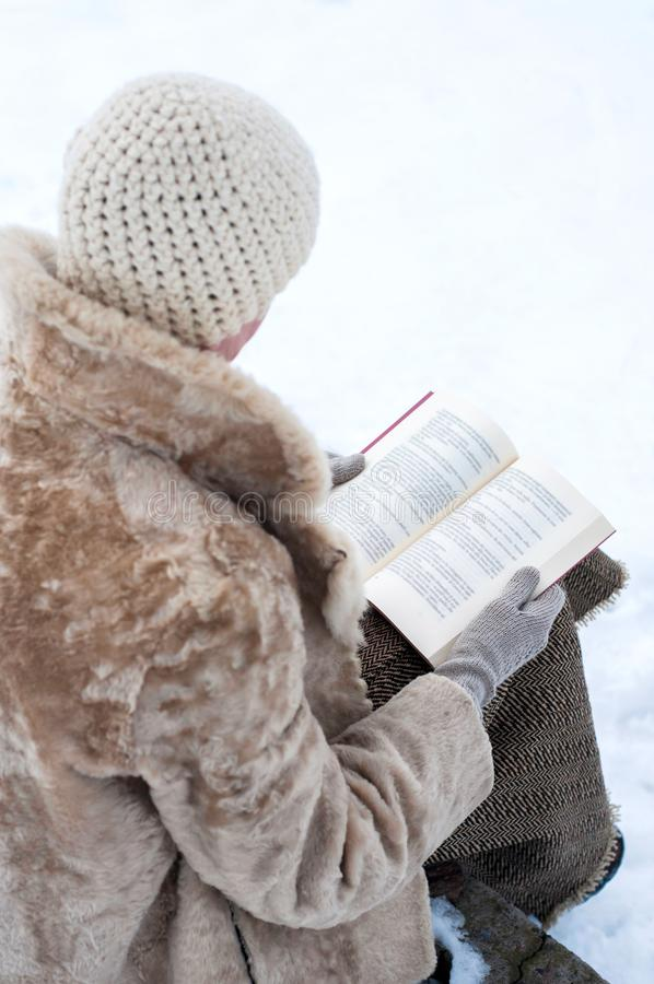 Woman ready a book in winter royalty free stock images