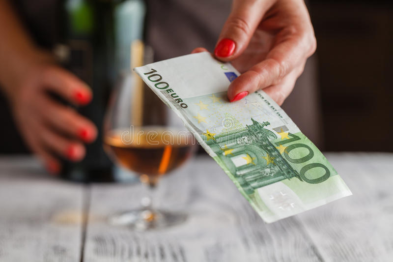 Woman ready to pay whiskey with euro banknotes stock photo