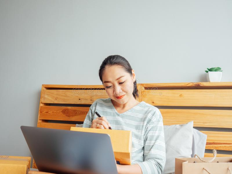 Woman ready to ship the products of her online store to the customer. Concept of work at home online business. Asian woman ready to ship the products of her stock images