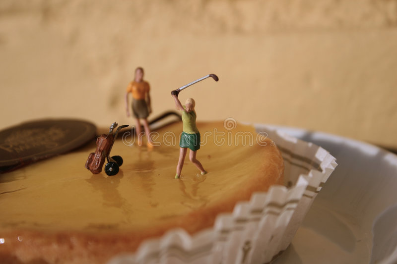 Woman ready to swing. Mini figurine playing golf, ready to swing royalty free stock image