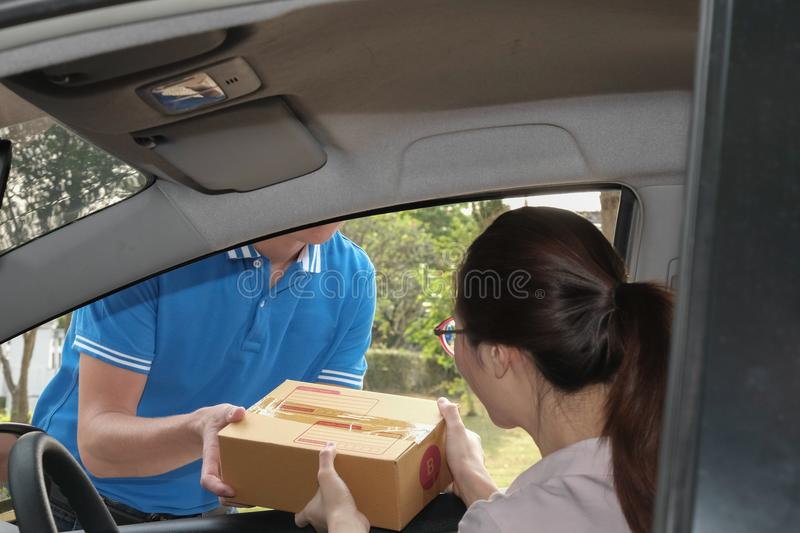 Woman receive package from delivery man. male postal courier per. Son deliver cardboard box to female adult on car royalty free stock images