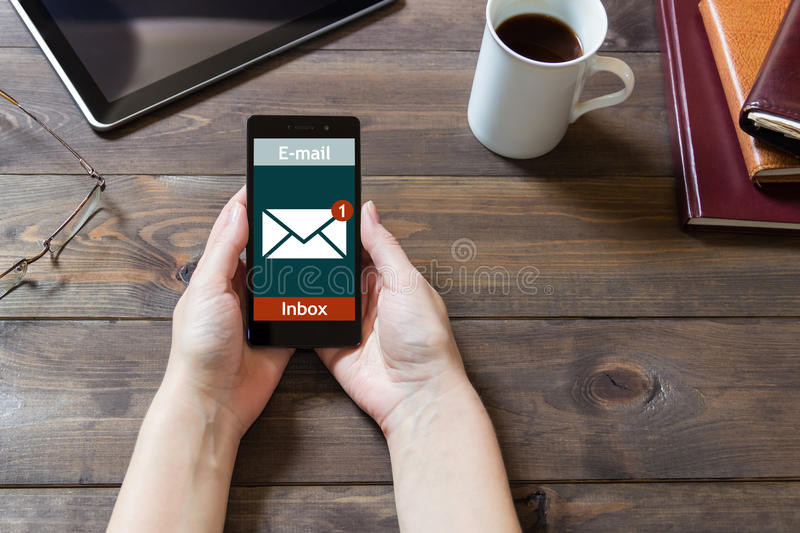 The woman received an e-mail online on a mobile phone. Message online icon. royalty free stock image