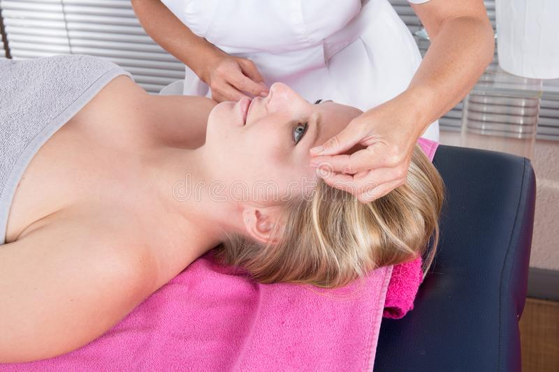 Girl Receiving An Anti-aging Acupuncture Needle Therapy royalty free stock image