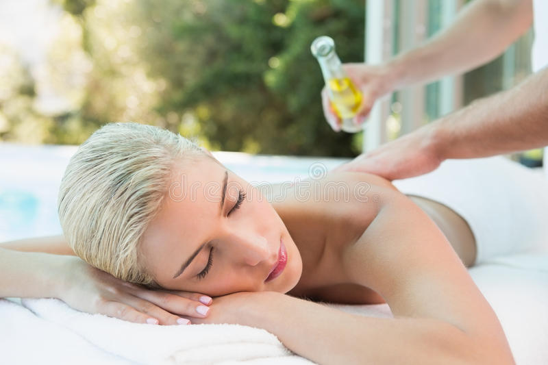 Woman receiving back massage at spa center. Close up of an attractive young woman receiving back massage at spa center royalty free stock photography