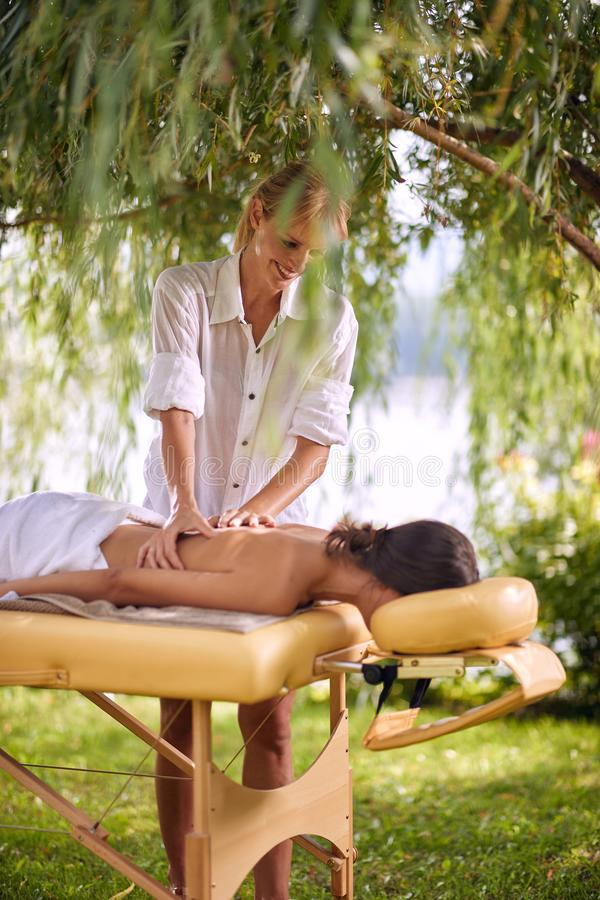 Woman receiving back massage at spa. Female having relaxing mass stock photos