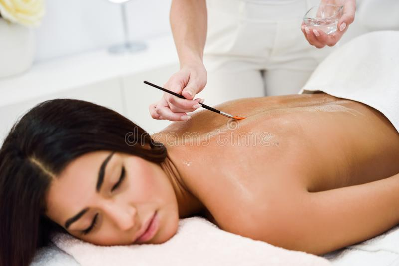 Woman receiving back massage treatment with oil brush in spa wellness center royalty free stock photo
