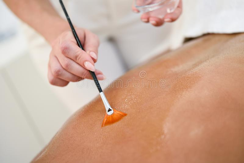 Woman receiving back massage treatment with oil brush stock image