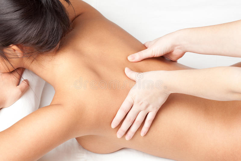 Woman receiving backmassage stock images