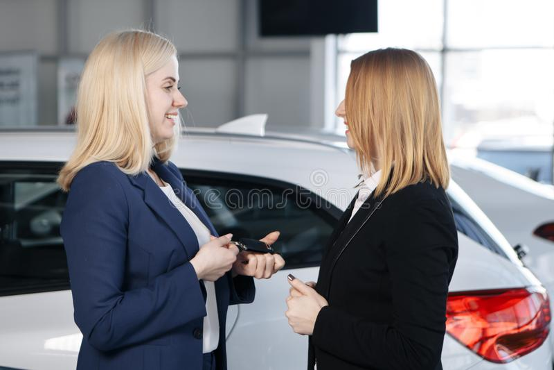 Woman receiving car keys from a dealer stock photography