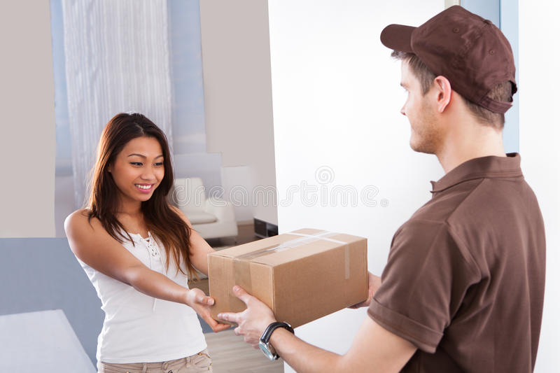 Woman receiving courier from delivery man. Smiling young women receiving courier from delivery men at home royalty free stock image