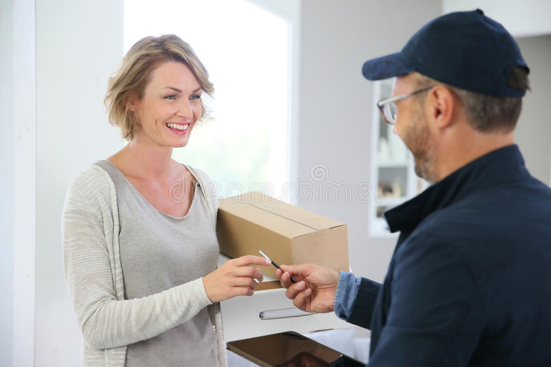 Woman receiving delivery man with package royalty free stock photos
