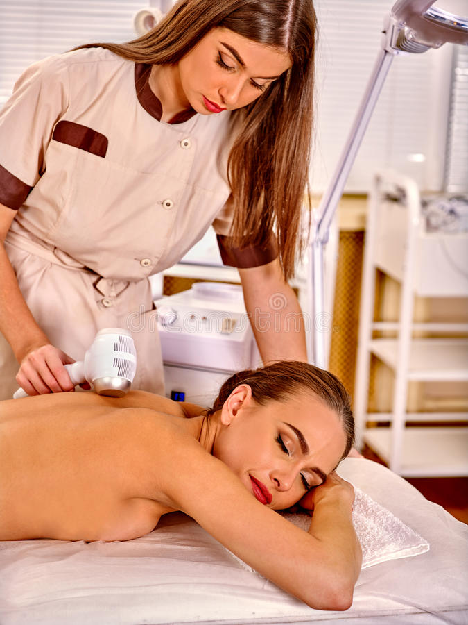 Woman receiving electricity microdermabrasion. Young white women receiving electric microdermabrasion massage at beauty salon. In room is device for hardware stock photos