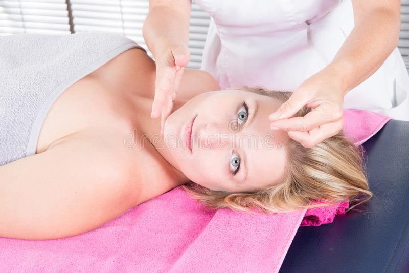 Woman receiving facial acupuncture treatment on young attractive girl royalty free stock image