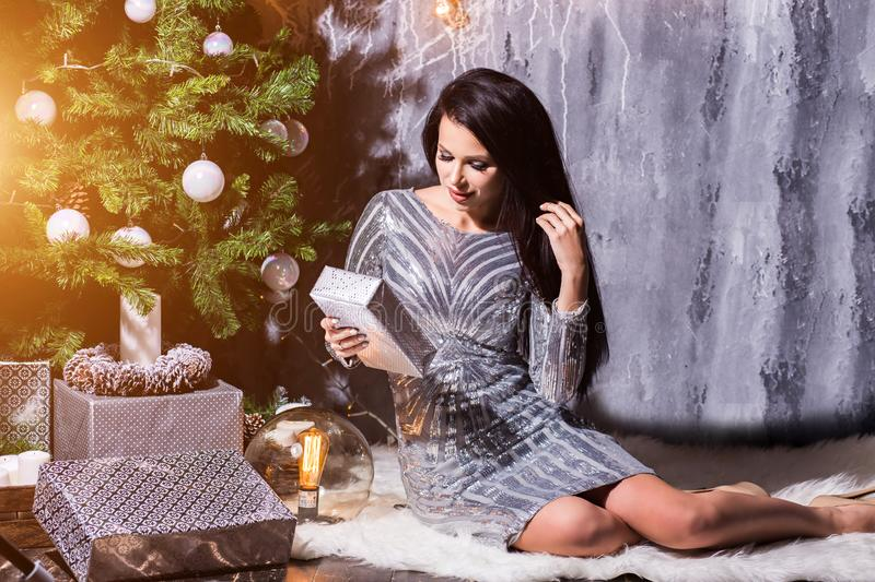 New Year`s and Christmas. Woman holds a lot of gifts near a Christmas tree. Woman receiving gifts under Christmas tree. New Year, holiday, celebration, winter stock image