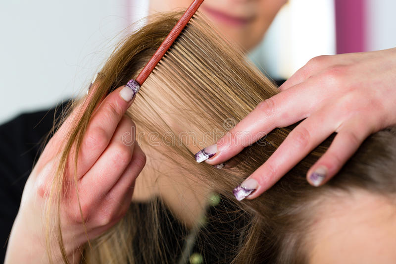 Woman receiving haircut in hairdressers shop stock image
