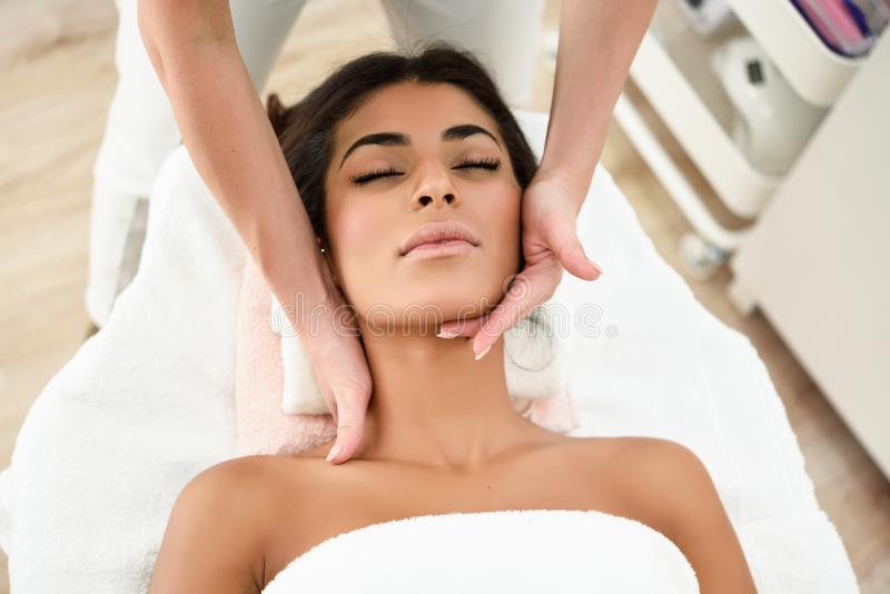 Woman receiving head massage in spa wellness center. Arab woman receiving head massage in spa wellness center. Beauty and Aesthetic concepts royalty free stock photography