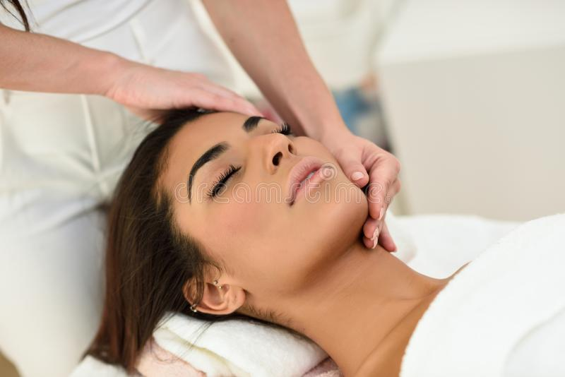 Woman receiving head massage in spa wellness center. Arab woman receiving head massage in spa wellness center. Beauty and Aesthetic concepts royalty free stock photos