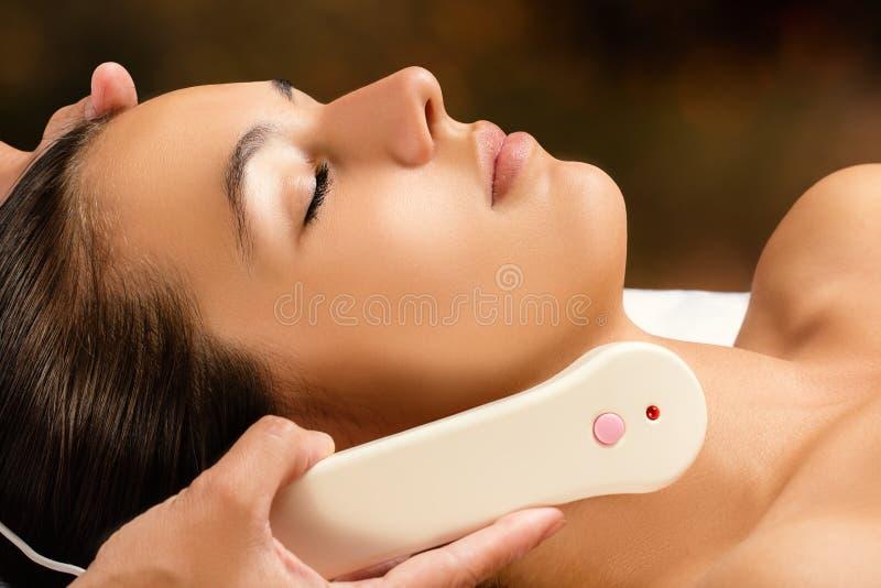 Woman receiving high frequency facial treatment. stock photos