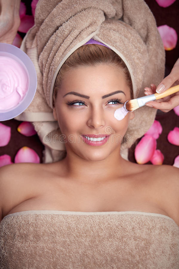 Woman receiving hydration facial mask. Young beautiful woman receiving hydration facial mask in spa beauty salon stock image