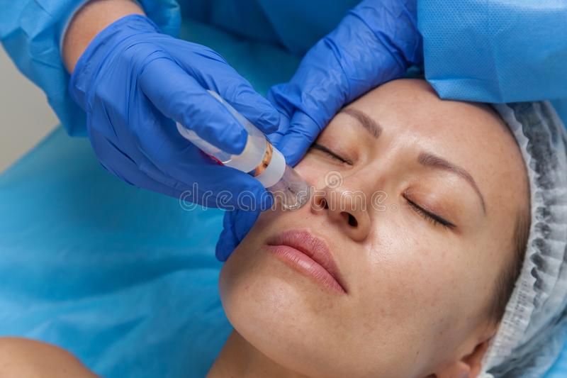 Woman receiving injection. Cosmetic treatment by injection in the clinic. Use of a dermal injector to stimulate the skin. A woman receives injections of a royalty free stock photography