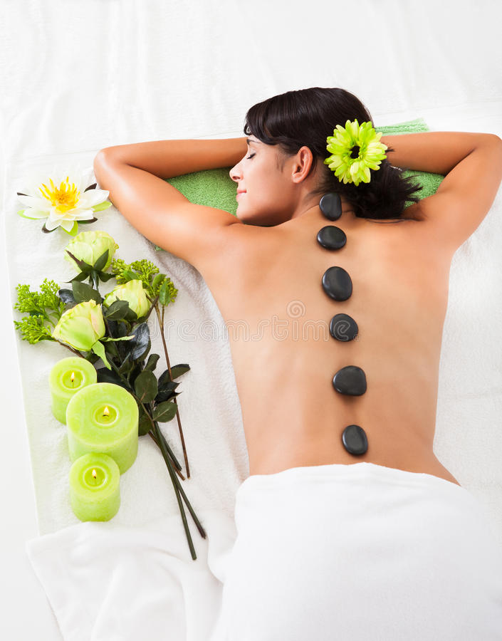 Woman receiving lastone massage stock images