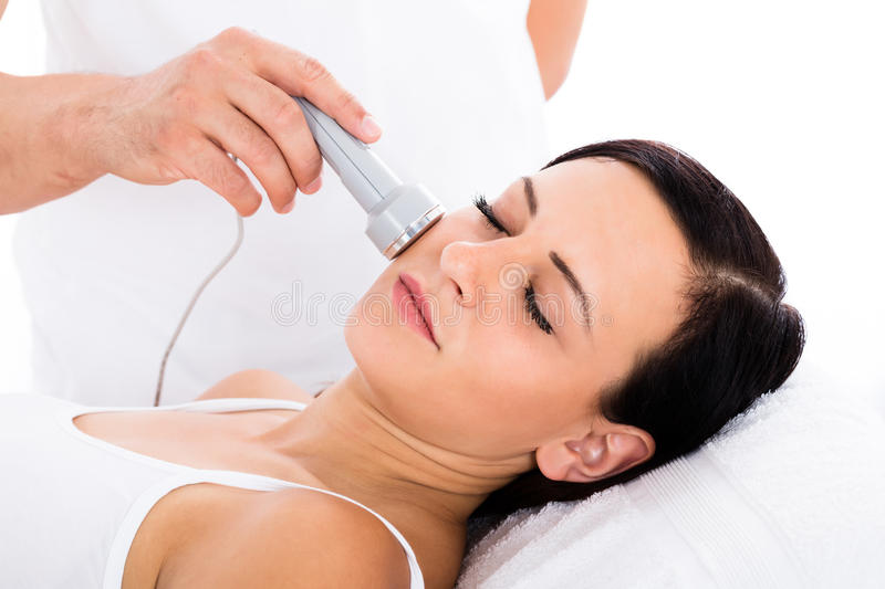 Woman Receiving Microdermabrasion Therapy On Forehead. Close-up Of A Relaxed Woman Receiving Microdermabrasion Therapy On Forehead stock photo
