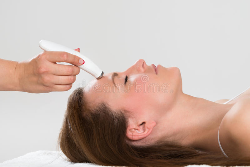 Woman Receiving Microdermabrasion Therapy. Young Woman Receiving Microdermabrasion Therapy In Beauty Clinic stock image