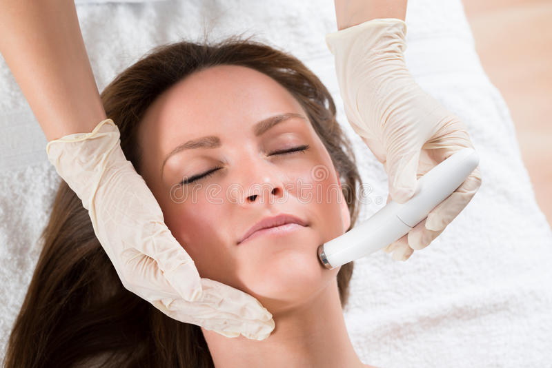 Woman Receiving Microdermabrasion Therapy. Young Woman Receiving Microdermabrasion Therapy In Beauty Clinic stock photography