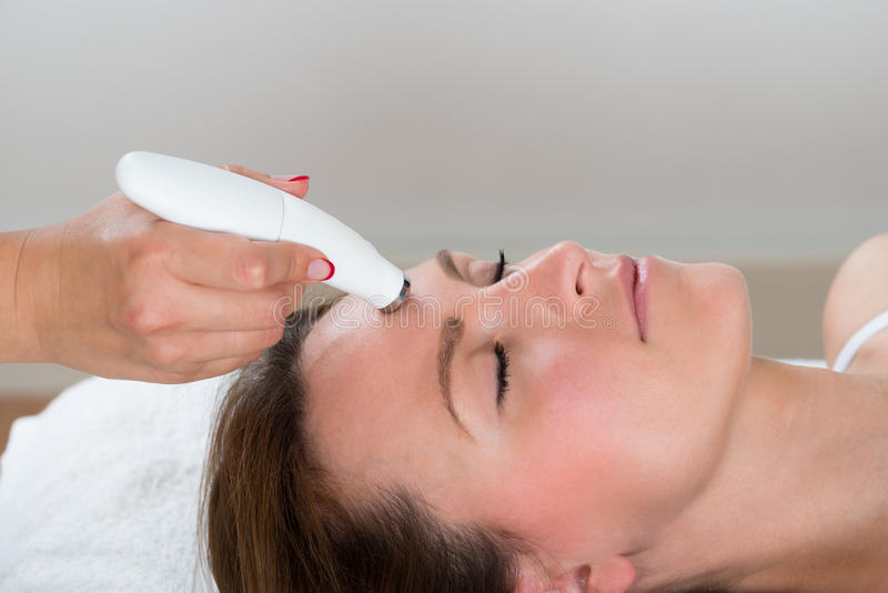 Woman Receiving Microdermabrasion Therapy. Young Woman Receiving Microdermabrasion Therapy In Beauty Clinic royalty free stock photos