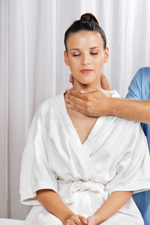 Woman Receiving Neck Massage. Relaxed young women in bathrobe receiving neck massage by male masseuse at health spa stock images