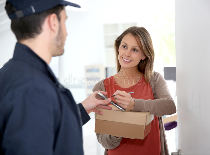 Woman receiving pacakage at home. Woman sigining electronic receipt of delivered package stock image