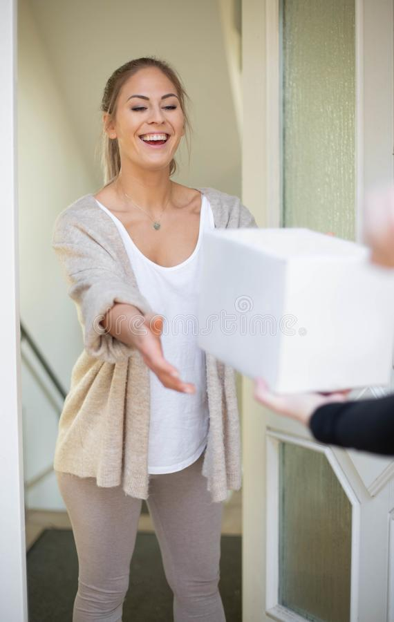 Woman receiving package box. From postman in front of house stock image