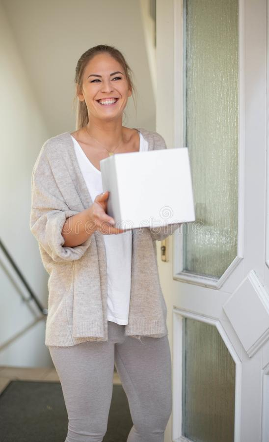 Woman receiving package box. From postman in front of house and smiles royalty free stock photography