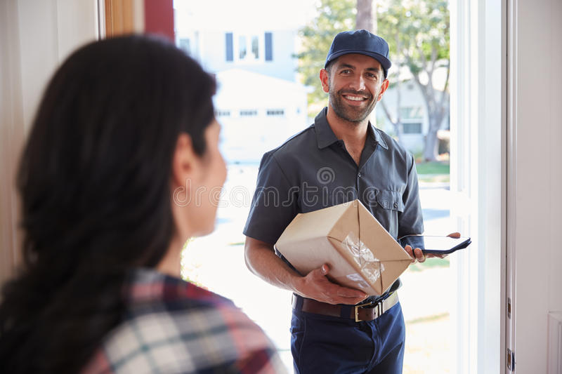 Woman Receiving Package From Courier At Home royalty free stock photos